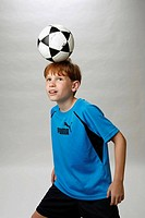 Red haired boy dominates a soccer ball