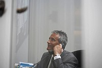 View through window of businessman using phone in office
