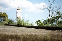 Woman wearing sun hat and summer dress, walking through grass and trees