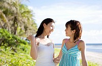Women chatting on beach, smiling