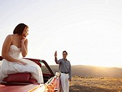 Groom taking photo of bride in convertible with PDA