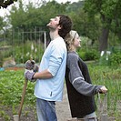 Man and woman on allotment looking at crops