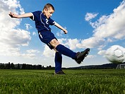 Boy 12-13 kicking football on pitch, side view, ground view
