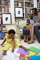 Family at home, girl 21-24 months drawing on floor