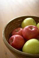 Red and green apples in wooden bowl on table, close-up