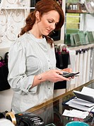 Young woman, owner of gift shop, standing behing checkout counter, using calculator