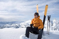 Skier resting in snow, looking at view, smiling
