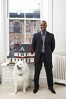 Businessman standing with dog by building model