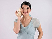 Woman holding seashell to her ear