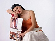 Portrait of a woman with eyes closed and holding a magazine