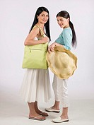 Two women holding sunhat and green handbag