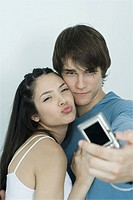 Young couple posing for photo, man holding out digital camera, portrait