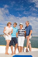 Family including mature and young couple on yacht