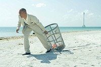 Man in suit pulling garbage can across sunny beach, full length