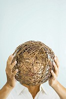 Man holding up wicker sphere in front of face
