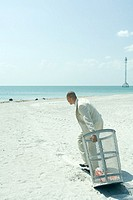 On beach, man in suit pulling garbage can towards ocean, side view, full length