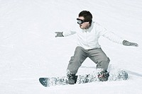 Young man snowboarding, action shot, full length