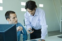 Two young businessmen looking at cell phone