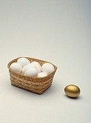 Single golden egg beside basket of white eggs