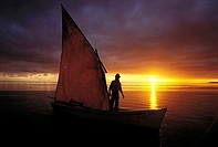 Mauritius, traditional fishing boat with sail at sunset