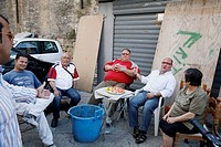 People sitting in a street in La Kalsa, Palermo, Sicily.