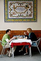 Couple sitting at an outdoors restaurant, El Centro area, Seville, Spain.