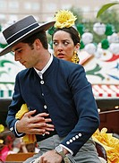 Couple wearing traditional costumes sitting on a horse at the April Fair, Seville, Spain.
