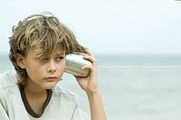 Boy holding tin can phone up to ear, looking away, portrait