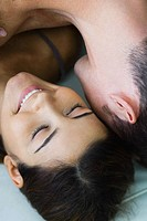 Man lying on top of woman, woman smiling, cropped view, close-up