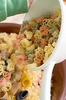 Child tipping coloured pasta out of strainer into bowl
