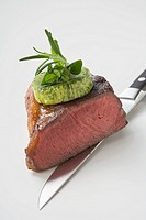 Beef steak with herb butter on knife showing cut edge