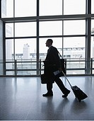 Businessman pulling luggage in airport, side view