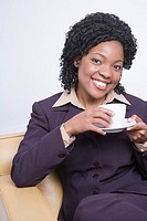 Young woman sitting, holding cup, smiling, portrait