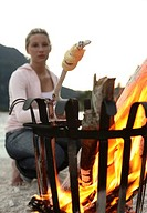 Woman, young, fires, fire basket, bread on a stick, blurred,