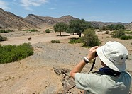 Tourists Viewing a Lone Elephant Loxodonta africana Through Binoculars  Hoanib River, Kaokoland, Namibia, Africa