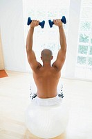 Man lifting weights on fitness ball (thumbnail)