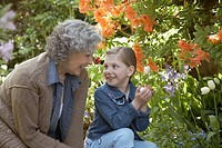 Grandmother and granddaughter together in garden