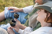 Couple relaxing outdoors with red wine