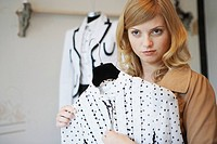 Woman holding blouse in clothing store (thumbnail)