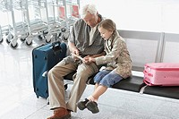 Grandfather and granddaughter sitting side by side in airport
