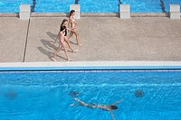 Three girls walking near swimming pool