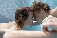 Boy and girl face to face underwater