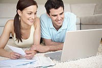 Young couple paying bills at home