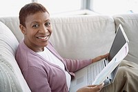 Woman on sofa with laptop and financial statement
