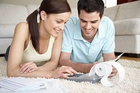 Young couple using adding machine at home
