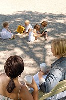 Women and children sitting in park