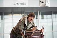 Traveler at airport with baggage cart