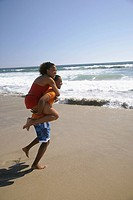 Husband carrying wife piggyback at beach