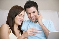 Couple using credit card and cell phone