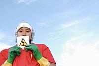 Woman holding hazardous warning, danger ´High Voltage´ notice.